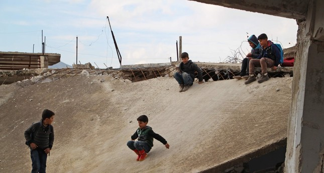 Syrian children slide down the collapsed roof of a bombarded school in Idlib province, Jan. 30, 2019.