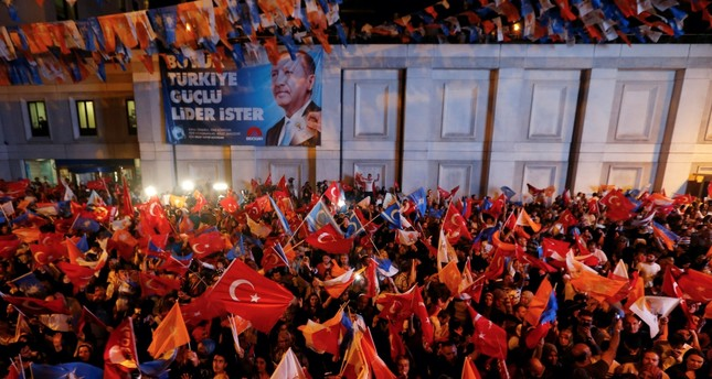 People waving flags to celebrate President Erdoğan's victory in presidential and parliamentary elections, outside his AK Party's headquarters, Istanbul, Sunday.