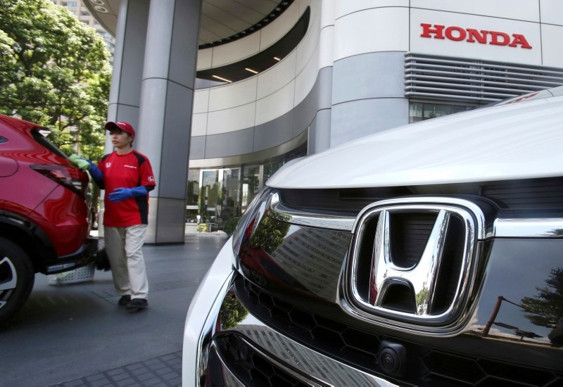 In this July 31, 2018, file photo, an employee of Honda Motor Co. cleans a Honda car displayed at its headquarters in Tokyo. (AP Photo)