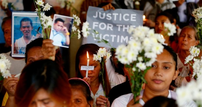 Relatives of victims in President Rodrigo Duterte's war on drugs hold lit candles and display portraits of their loved ones as they gather at a Roman Catholic church in suburban Quezon city northeast of Manila, Philippines, March 15, 2019. (AP Photo)