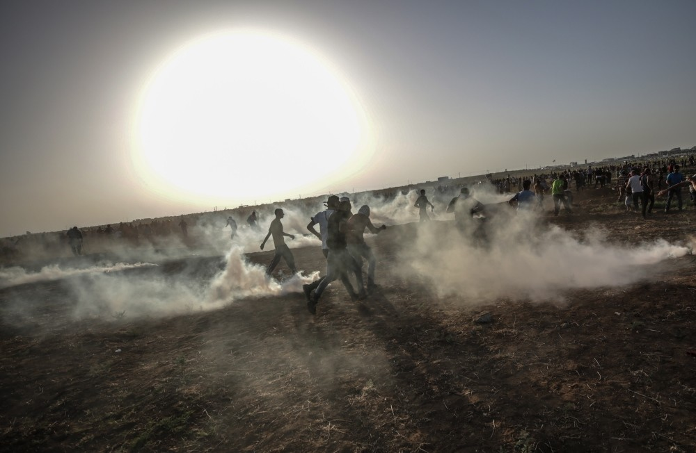 Palestinians protesters run for cover from Israeli tear-gas during clashes after a protest near the border, Gaza City, June 22.