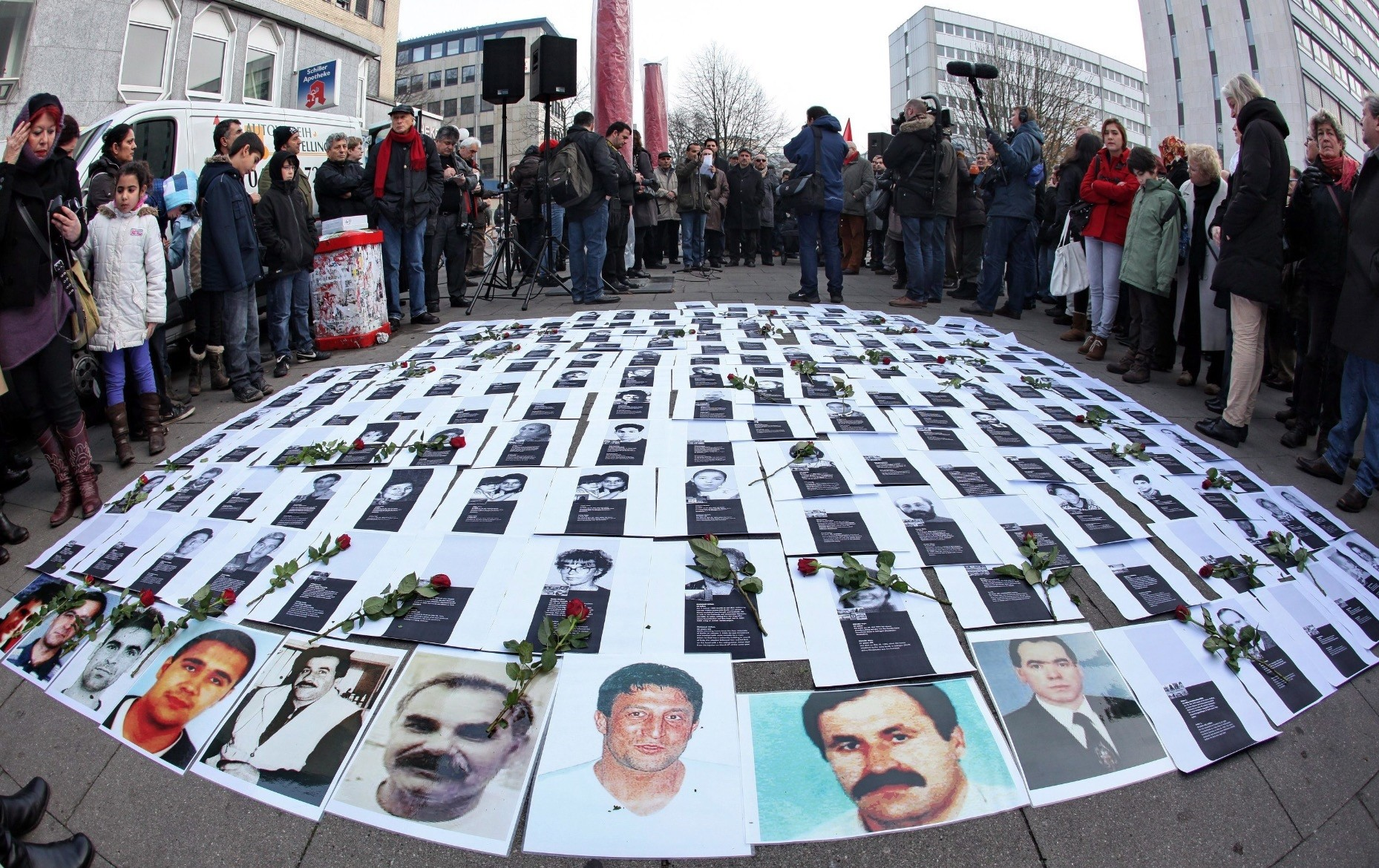 Photos of neo-Nazi violence victims lie in Germany on a street, with NSU victims on the front row, during a protest in Hamburg in 2011.