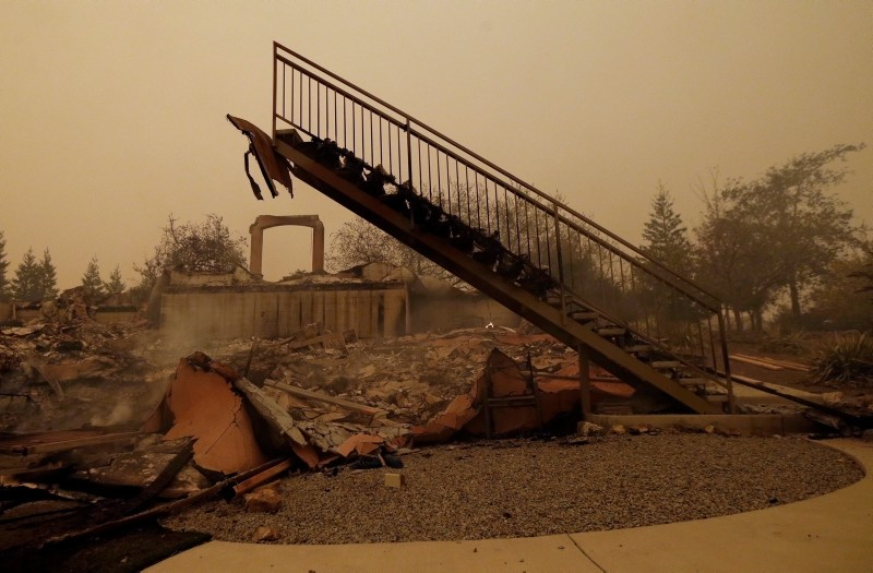 In this Friday, Nov. 9, 2018, file photo a staircase that once led to another level is seen among the burned remains of home that was destroyed by a wildfire that swept through the area in Paradise, Calif. (AP Photo)