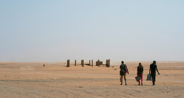 Three men head north towards Algeria after crossing the Assamaka border post in northern Niger on Sunday, June 3, 2018. (AP Photo)