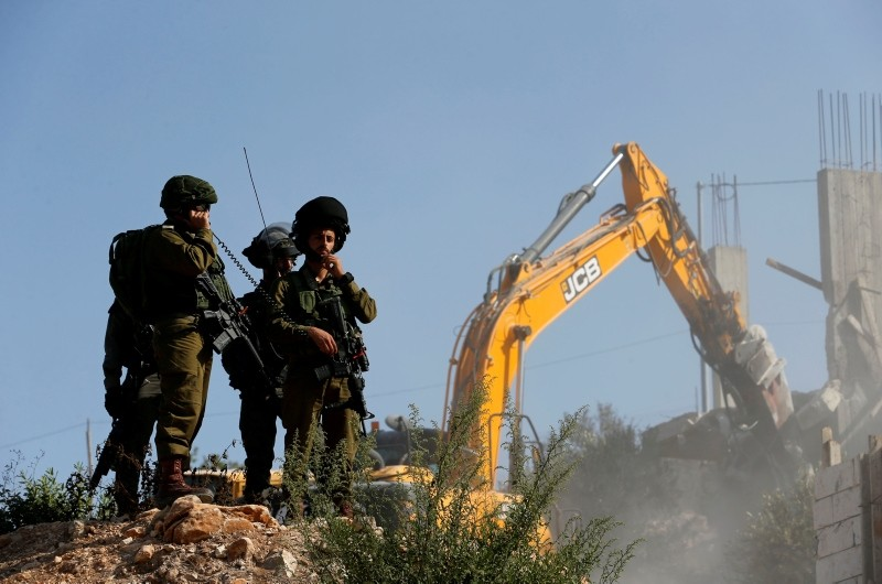 Israeli soldiers stand guard as machinery demolishes Palestinian houses in the village of Al-Walaja near Bethlehem, in the occupied West Bank, Sept. 3, 2018. (Reuters Photo)