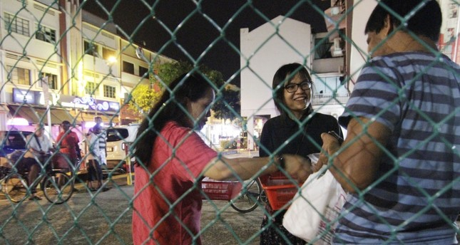 Freegans Joan-ann Chua and Chan Pei Ting give out leftovers to a migrant worker.