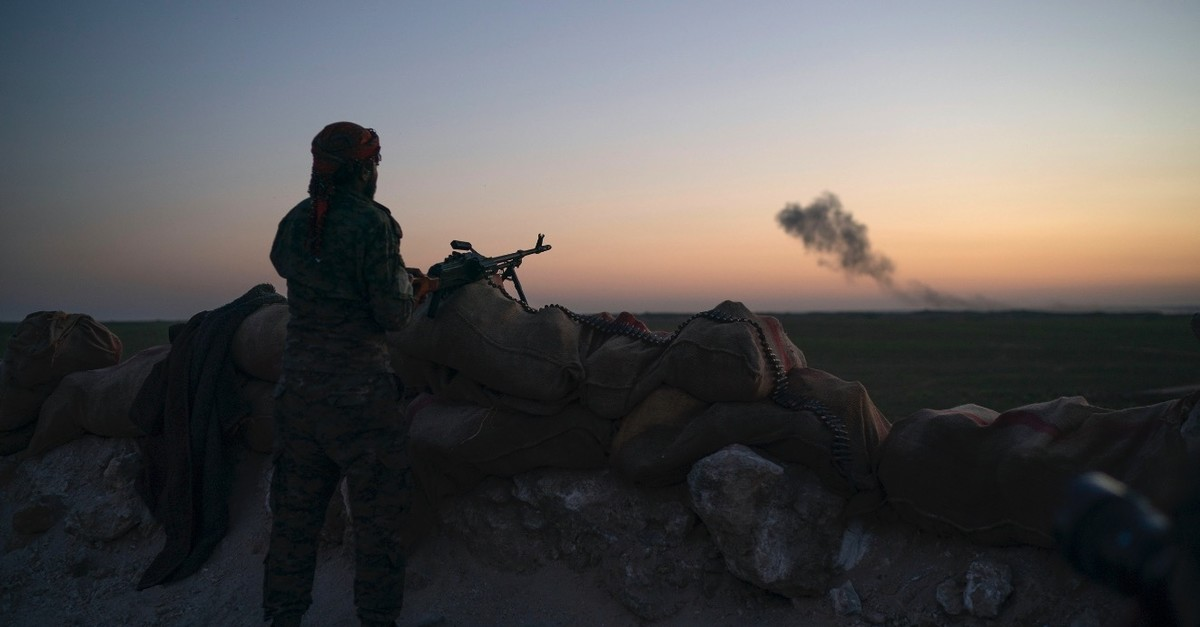 A terrorist from the U.S.-backed and YPG-dominated Syrian Democratic Forces (SDF) scans the desert outside of Baghouz, Syria, Feb. 19, 2019.