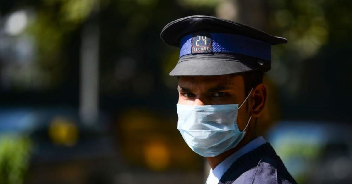 A private security guard wearing a protective face mask amid concerns over the COVID-19 coronavirus outbreak stands an the entrance to a hotel in New Delhi, Feb. 13, 2020. (AFP Photo)