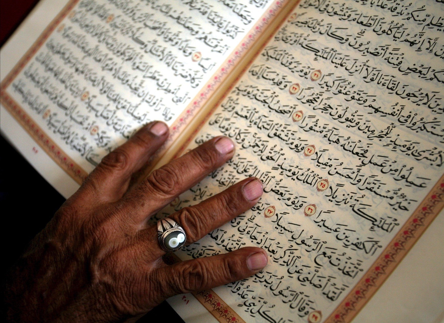 An elderly man touches pages of the Quran as he reads it after noon prayers on the second day of the Muslim holy month of Ramadan in Amman.