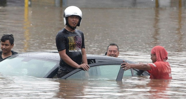 Residents push a submerged car on a flooded street in Jakarta, Indonesia, 01 January 2020. Overnight heavy rains triggered widespread flooding in Jakarta and surrounding areas, bringing traffic to a standstill.  EPA-EFE Photo