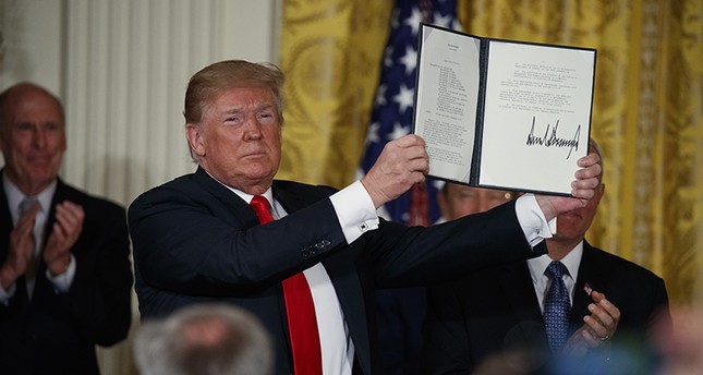 President Donald Trump shows off a Space Policy Directive after signing it during a meeting of the National Space Council in the East Room of the White House, Monday, June 18, 2018, in Washington. AP Photo