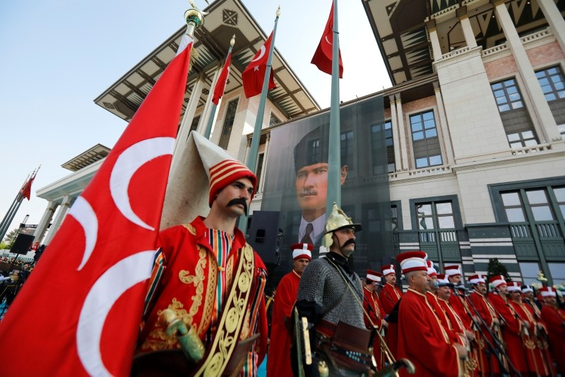 Actors dressed in Ottoman-era warriors' attire stands outside the Presidential Complex decorated with a poster of modern Turkey founder Mustafa Kemal Atatürk, in Ankara.