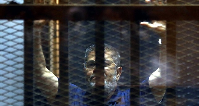 A file photo dated 02 June 2015 shows ousted Egyptian President, Mohamed Morsi gesturing from inside a cage in the courtroom where he stood trial in Cairo, Egypt (EPA File Photo)