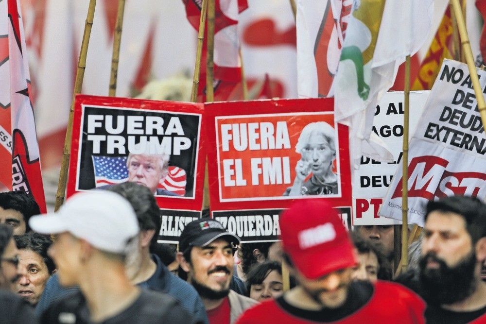 Protesters with signs bearing the faces of President Donald Trump and IMF chief Christine Lagarde march against the G20 summit being held in Buenos Aires, Argentina, Nov. 30.