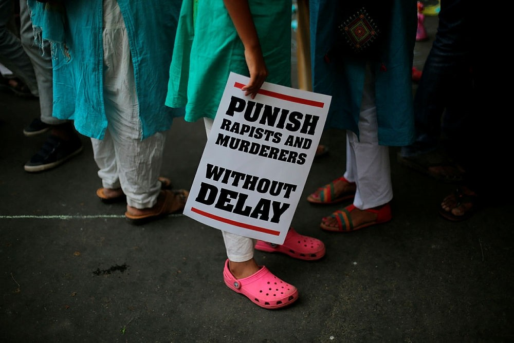 In this April 15, 2018 file photo, an Indian protestor stands with a placard during a protest against two recently reported rape cases as they gather near the Indian parliament in New Delhi, India. (AP Photo)