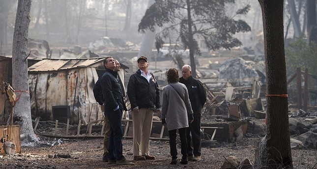 Gov.-elect Gavin Newsom, FEMA Director Brock Long, President Donald Trump, Paradise mayor Jody Jones, Gov. Jerry Brown tour the Skyway Villa Mobile Home and RV Park, during Trump's visit of the Camp Fire in Paradise, Calif., Nov. 17, 2018. (AP Photo)