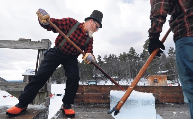 With a tip of his hat to the old-fashioned sartorial style of ice harvesters long ago, Jon Spence dresses the part while sliding ice onto a truck bed on Squam Lake, Jan. 16, 2019.