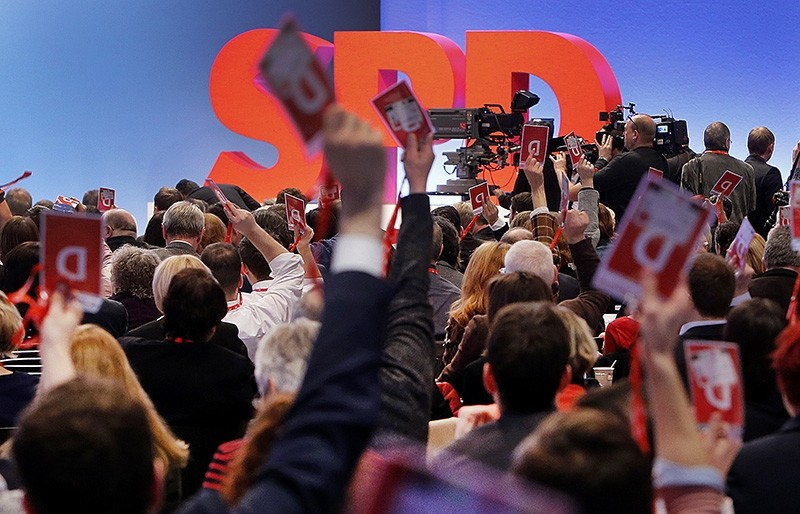 Delegates raise their cards for a poll during a party meeting of the Social Democrats, SPD, who are discussing the possible coalition talks with Chancellor Angela Merkel's conservatives in Bonn, Germany, Sunday, Jan. 21, 2018. (AP Photo)