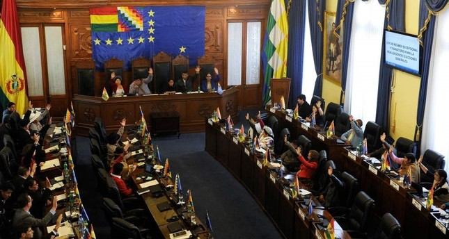 Senators vote during a session at Bolivia's Congress in La Paz, on November 23, 2019. - Bolivia's Congress will vote on a proposal Saturday that could open the door to new elections in the crisis-hit country, as the caretaker government prepares to meet with protesters to end weeks of unrest. (Photo by JORGE BERNAL / AFP)