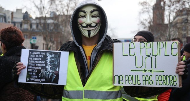A protester wearing a Guy Fawkes mask and a yellow vest holds a placard reading 'united people can't lose' during a march on February 2, 2019 in Paris. (AFP Photo)