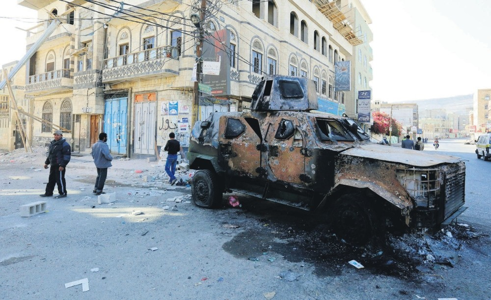 Yemenis walk past a destroyed armored personnel carrier in a street leading to the residence of Yemen's former president Ali Abdullah Saleh a day after Houthi militants killed him, Dec. 5.