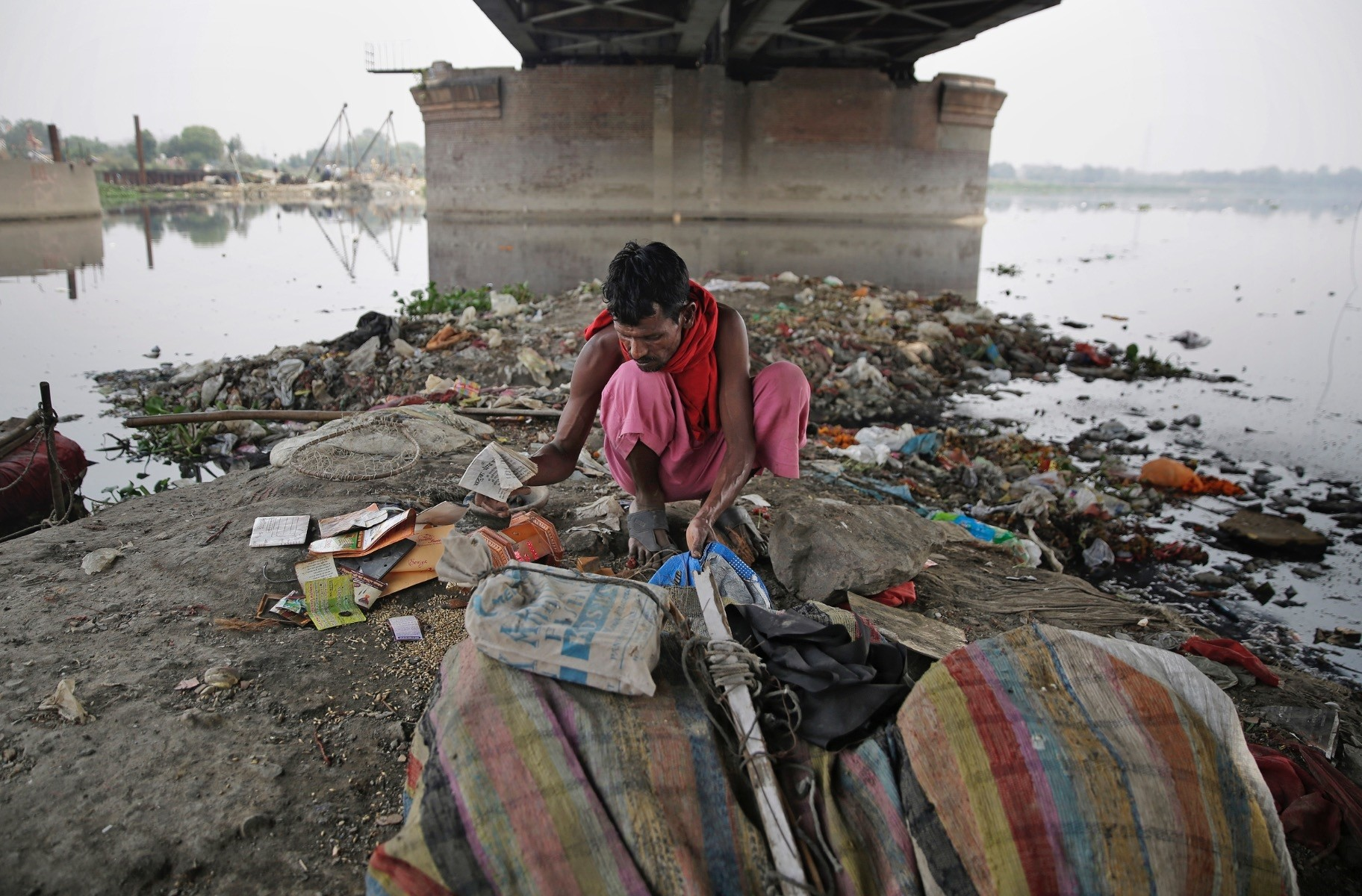 Ram Nath, 40, sorts reusable trash he fished out from Yamuna, Indiau2019s sacred river that flows through the capital of New Delhi.