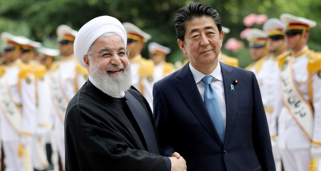Japanese Prime Minister Shinzo Abe, right, shakes hands for the cameras with Iranian President Hassan Rouhani, during the official arrival ceremony, at the Saadabad Palace in Tehran, Iran, Wednesday, June 12, 2019. (AP Photo)