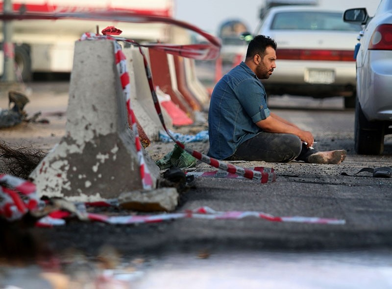 An Iraqi man sits on the tarmac at the site of  a car bomb attack, in the southern Iraqi city of Basra. (AFP Photo)