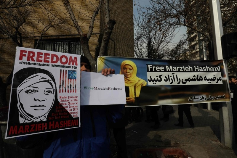 Iranians hold banners bearing messages that call for the release of US-born journalist Marzieh Hashemi, near the Swiss embassy in the capital Tehran on January 20, 2019 (AFP Photo)