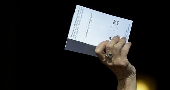 A Pro-referendum demonstrator brandishes a ballot outside Barcelona's university during a demonstration in Barcelona on September 24, 2017. (AFP Photo)