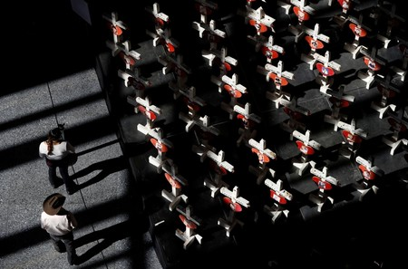 In this Sept. 25, 2018, file photo, people look at a display of wooden crosses and a Star of David on display at the Clark County Government Center in Las Vegas. (AP Photo)