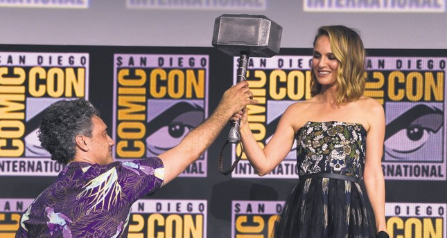 Director Taika Waititi hands the Thor hammer to Natalie Portman during the Thor Love And Thunder portion of the Marvel Studios panel on day three of Comic-Con International on July 20, 2019, in San Diego.