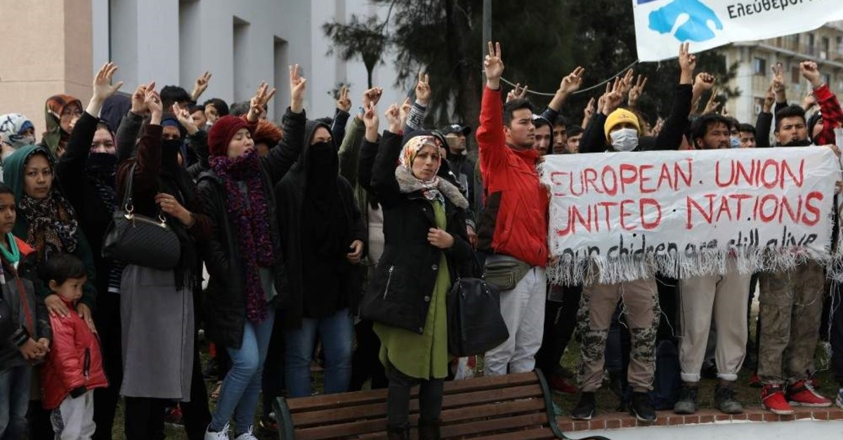 Refugees and migrants hold a banner and shout slogans outside the municipal theater of the city of Mytilene, Lesbos, Feb. 4, 2020. (REUTERS Photo)