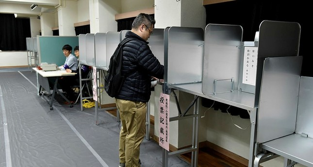 A man fills in his ballot to vote in Japan's general election at a polling station in Tokyo, Japan, Oct. 22, 2017. (AFP Photo)