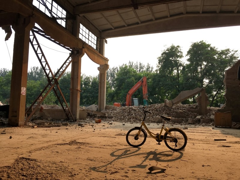A shared bike is seen inside the demolished building, Chinese artist Ai Weiwei's ,Left and Right, art studio since 2006, next to an excavator, in the northeast Beijing suburbs, China August 4, 2018. (Reuters Photo)