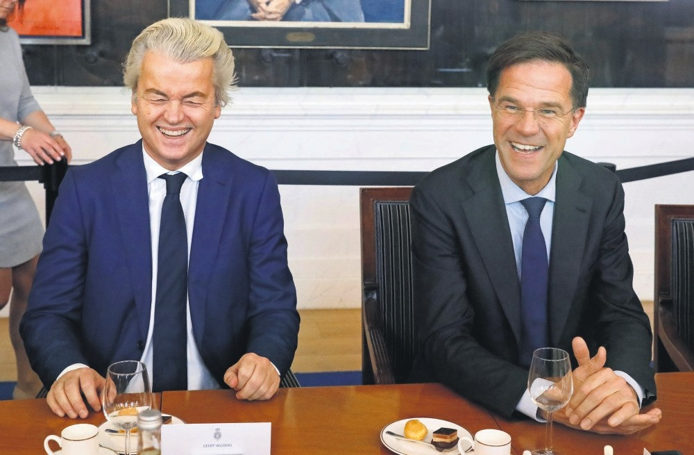 Dutch PM Mark Rutte (R) of the VVD party and Dutch far-right politician Geert Wilders of the PVV Party take part in a meeting at the Dutch Parliament, March 16.