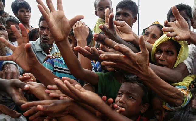 Rohingya refugees reach for food aid at the Kutupalong refugee camp in Ukhiya near the Bangladesh-Myanmar border.  At least 18,500 Rohingya had crossed into Bangladesh since fighting erupted in neighboring Myanmar's Rakhine state six days earlier.