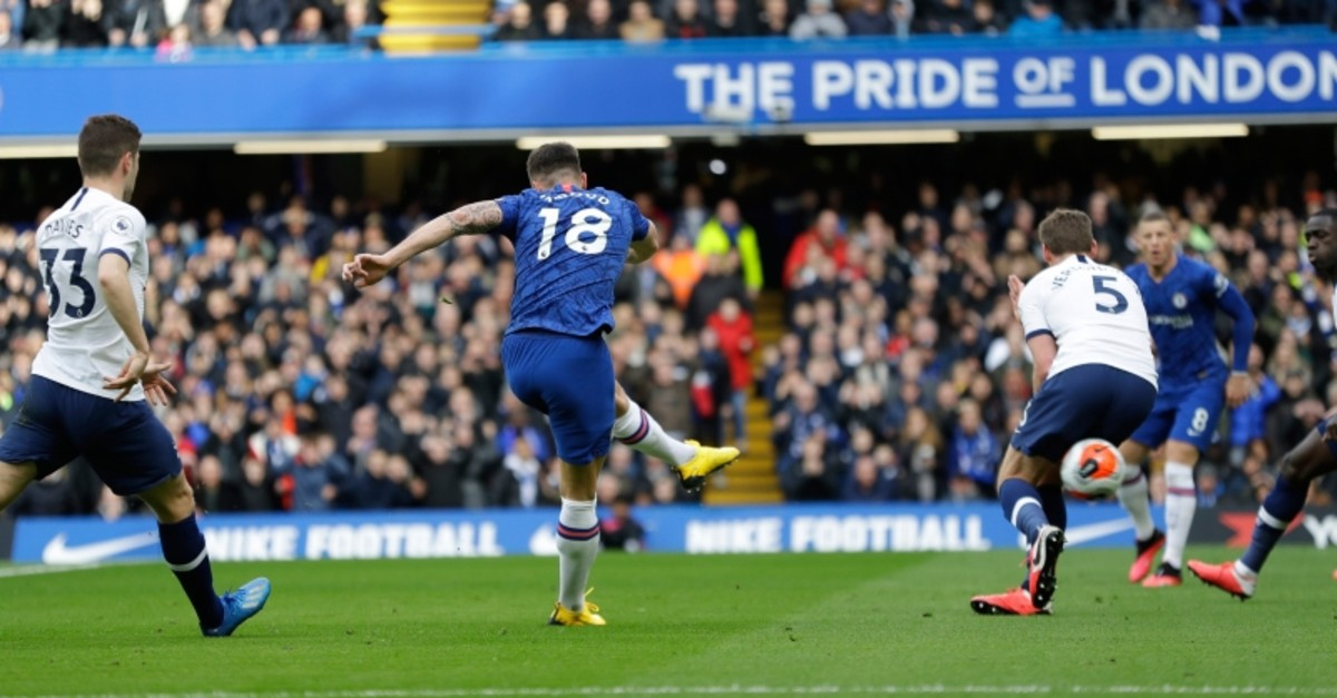 Chelsea's Olivier Giroud kicks the ball past Tottenham Hotspur defenders to score a goal during their English Premier League soccer match in London, England, Saturday, Feb. 22, 2020. (AP Photo)