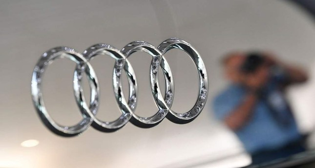 A photographer is reflected next to the logo of German carmaker Audi at the company's annual shareholders' meeting in Neckarsulm, Germany, May 23, 2019. (AFP Photo)