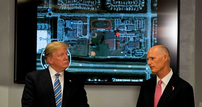 U.S. President Donald Trump (L) speaks with Florida governor Rick Scott while visiting first responders at Broward County Sheriff's Office in Pompano Beach, FL, Feb.16.