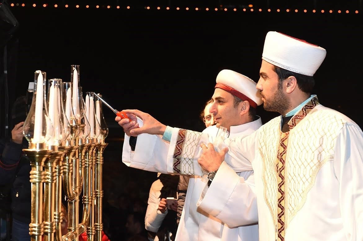 A Muslim imam helps a Jewish rabbi light a Hanukkah candle at an event in Istanbul in 2015, the first time Hanukkah was marked in public in the country.
