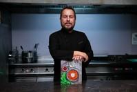 الشيف التركي يونس إمرة أكور مع كتابه مطبخ قيصري من الماضي إلى المستقبل (الأناضول)