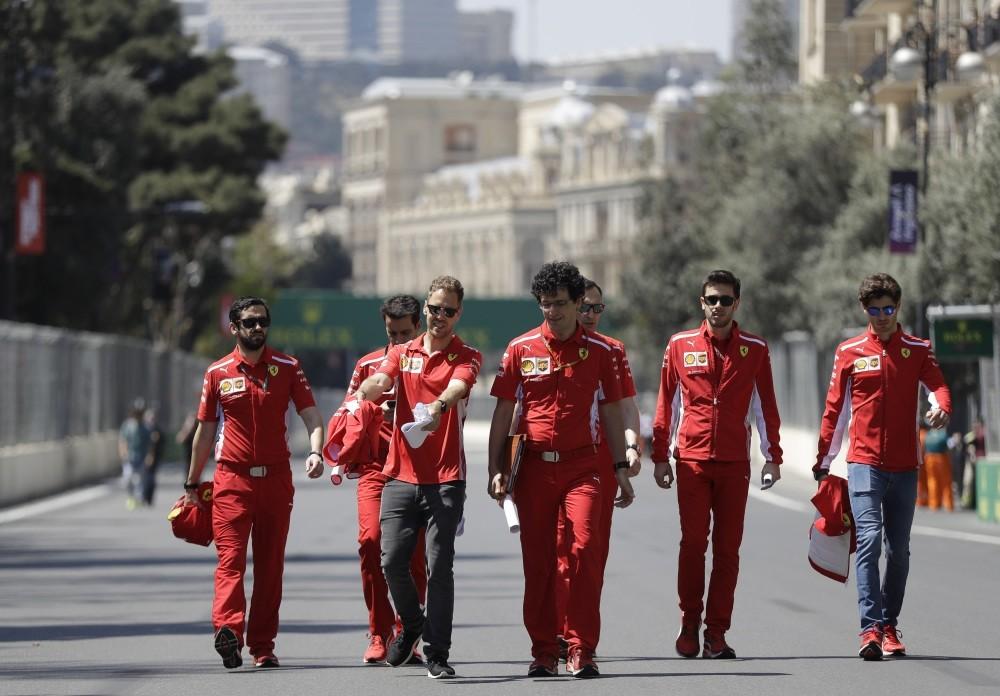 Ferrari driver Sebastian Vettel of Germany gestures as he walks flanked by team members at the Baku Formula One city circuit, in Baku, Azerbaijan, yesterday.