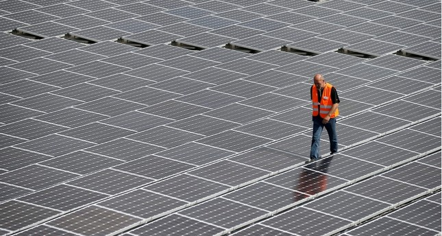 A file photograph showing a man walking between solar cell panels during the commissioning of the largest solar power plant in Neuendorf, Canton Solothurn, Switzerland, 20 August 2013. (EPA Photo)