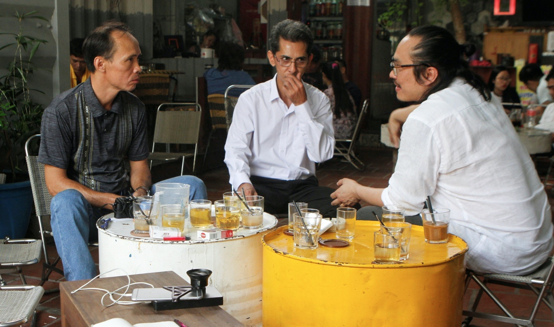 Vietnamese deportees and Amerasians Bui Thanh Hung (L) and Pham Chi Cuong (C) speak to U.S. lawyer and Vietnamese-American Tin Nguyen at a cafe in the suburbs of Ho Chi Minh City, Vietnam, April 19.