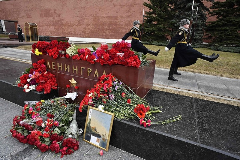 Flowers left in tribute to the victims of the April 3 blast in the Saint Petersburg metro are seen at a memorial stone reading Leningrad by the Kremlin wall as honour guard soldiers march in central Moscow on April 4, 2017. (AFP Photo)