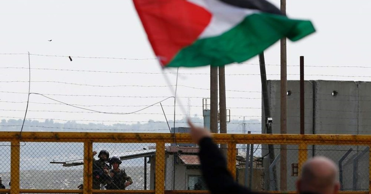 A Palestinian protester waves his national flag in front of Israeli security forces during Land Day commemorations outside the compound of the Israeli-run Ofer prison near Betunia in the Israeli-occupied West Bank on March 30, 2016. (AFP Photo)