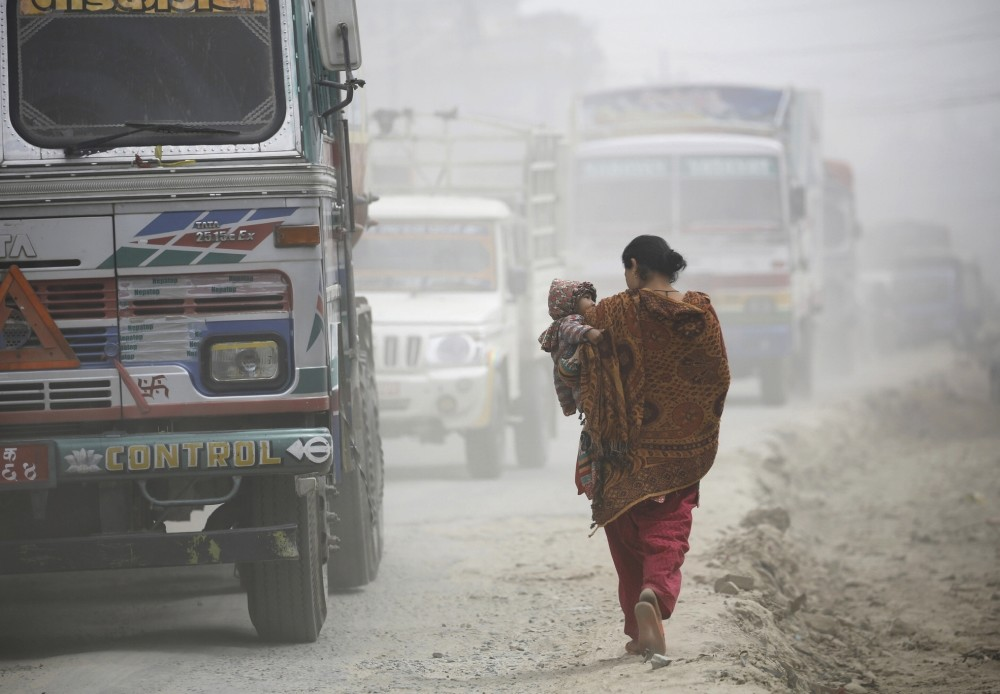 A woman carrying her child walks along the dusty road in Kathmandu.