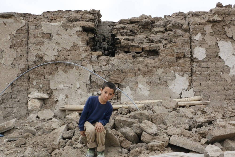 Arda poses in front of his collapsed house.