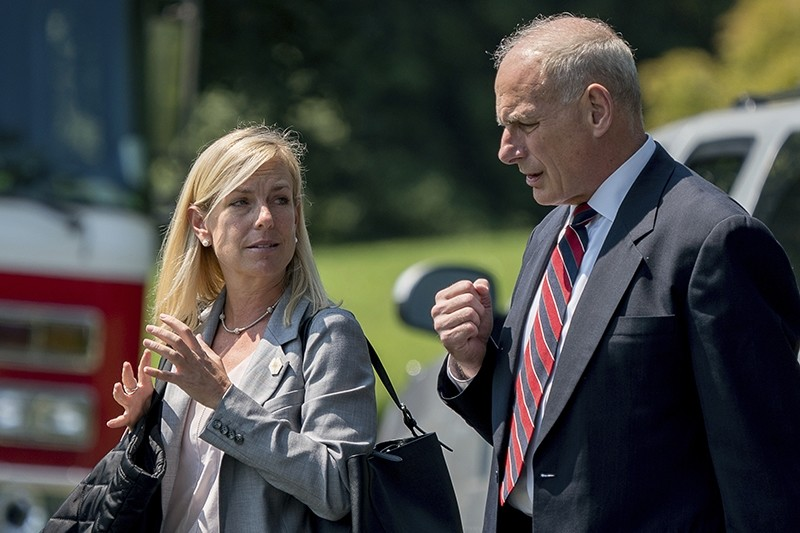 In this Aug. 22, 2017 photo, White House Chief of Staff John Kelly and Deputy Chief of Staff Kirstjen Nielsen speak together on the South Lawn of the White House in Washington. (AP Photo)